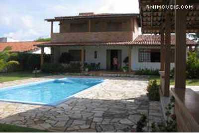 Frente da casa com piscina e jardim